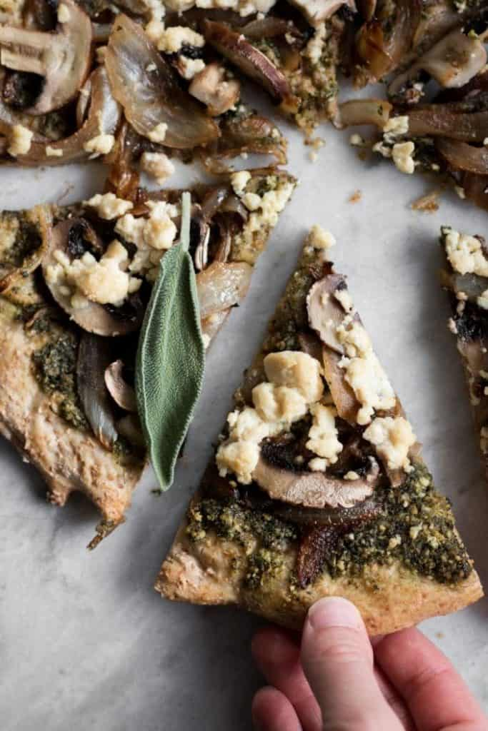 hand taking slice of pizza with sage pesto