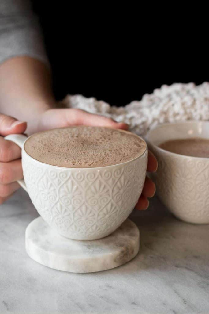hands holding cup of hot cocoa