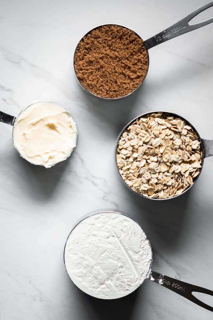 oats, flour, brown sugar and butter in measuring cups