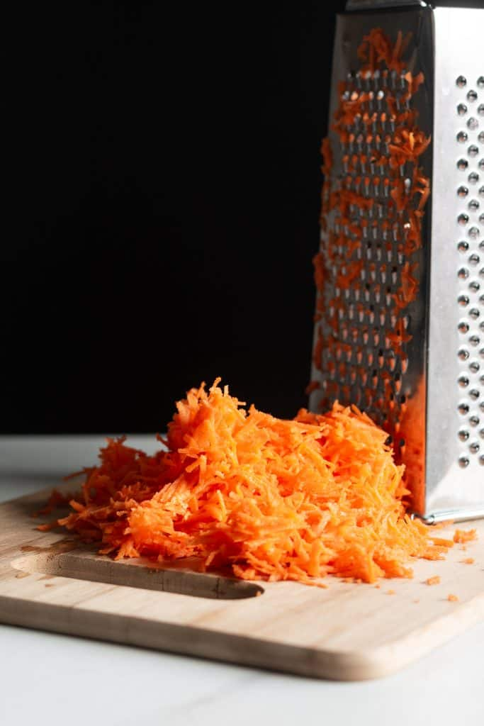 shredded carrots next to a grater