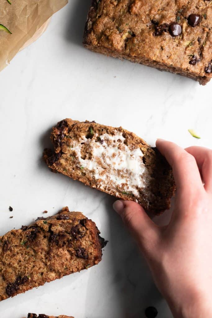 hand holding a slice of zucchini bread with butter