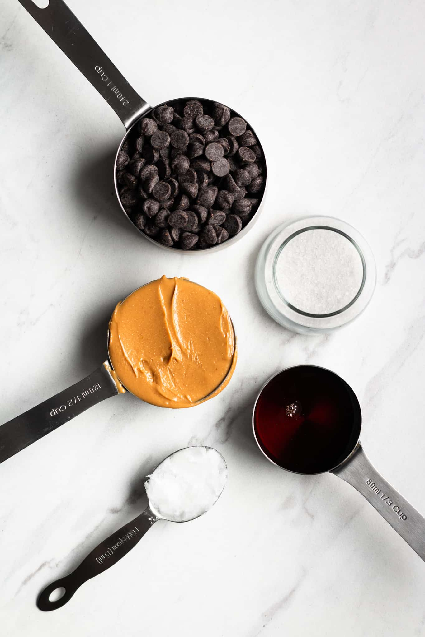 peanut butter, chocolate, salt, maple and coconut oil in measuring cups