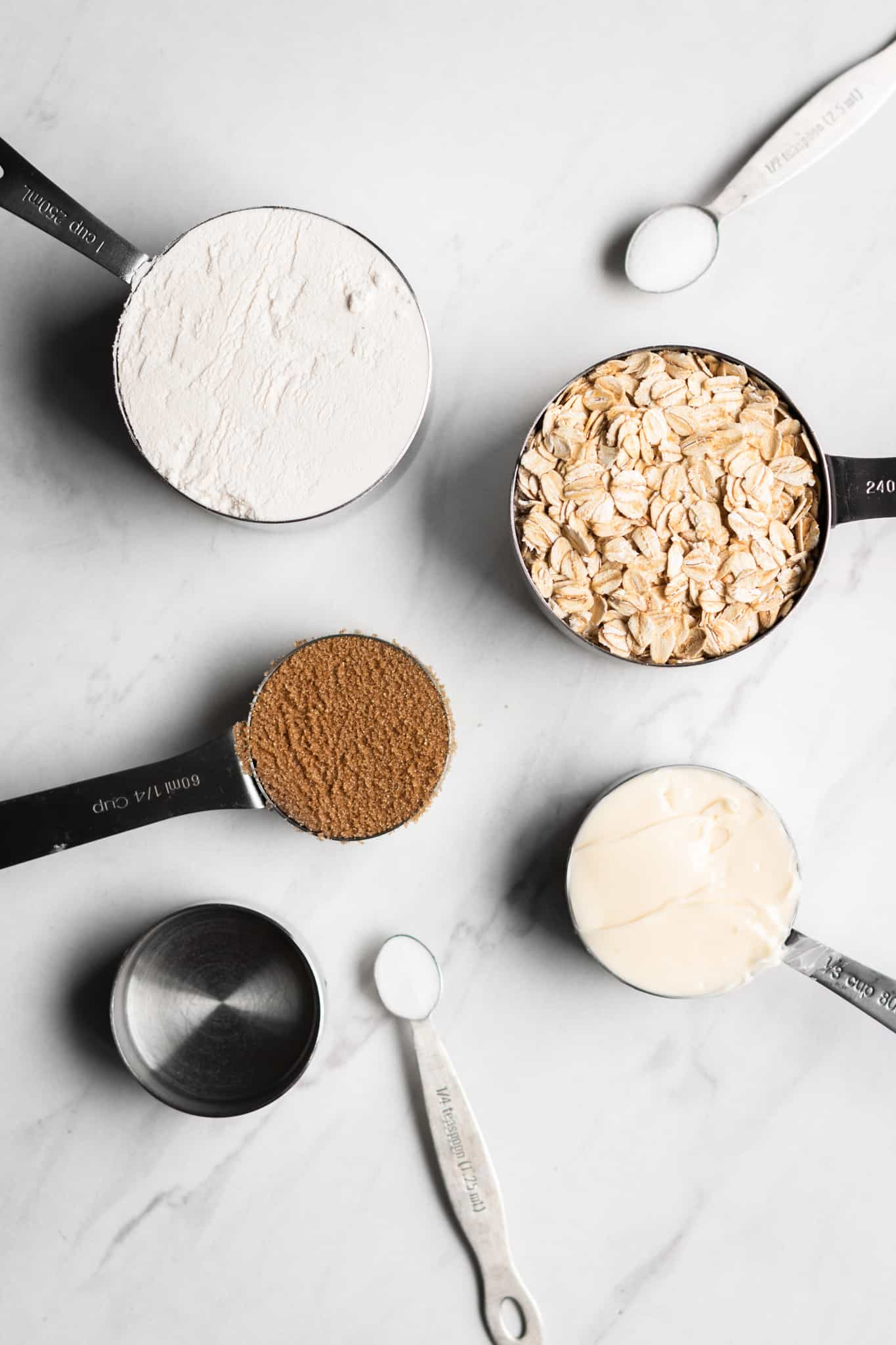 oats, flour, sugar and butter in measuring cups