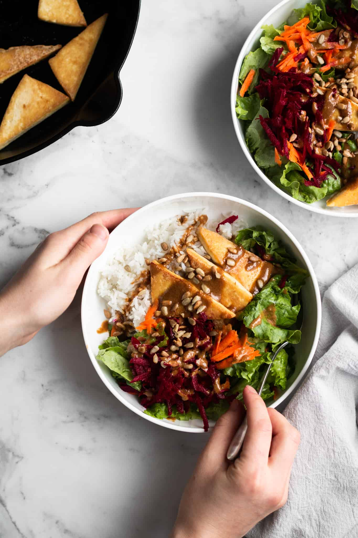 hands holding a bowl of cozy winter salad with tofu and rice
