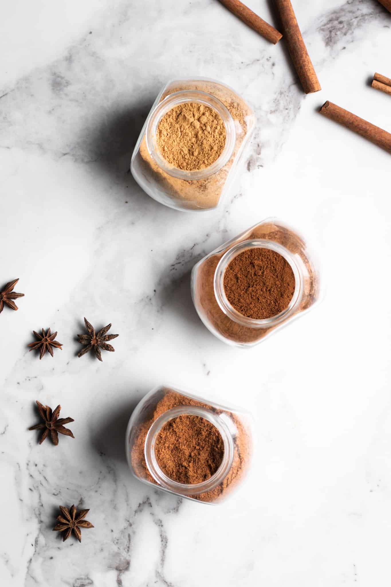 spices in jars with cinnamon sticks and star anise