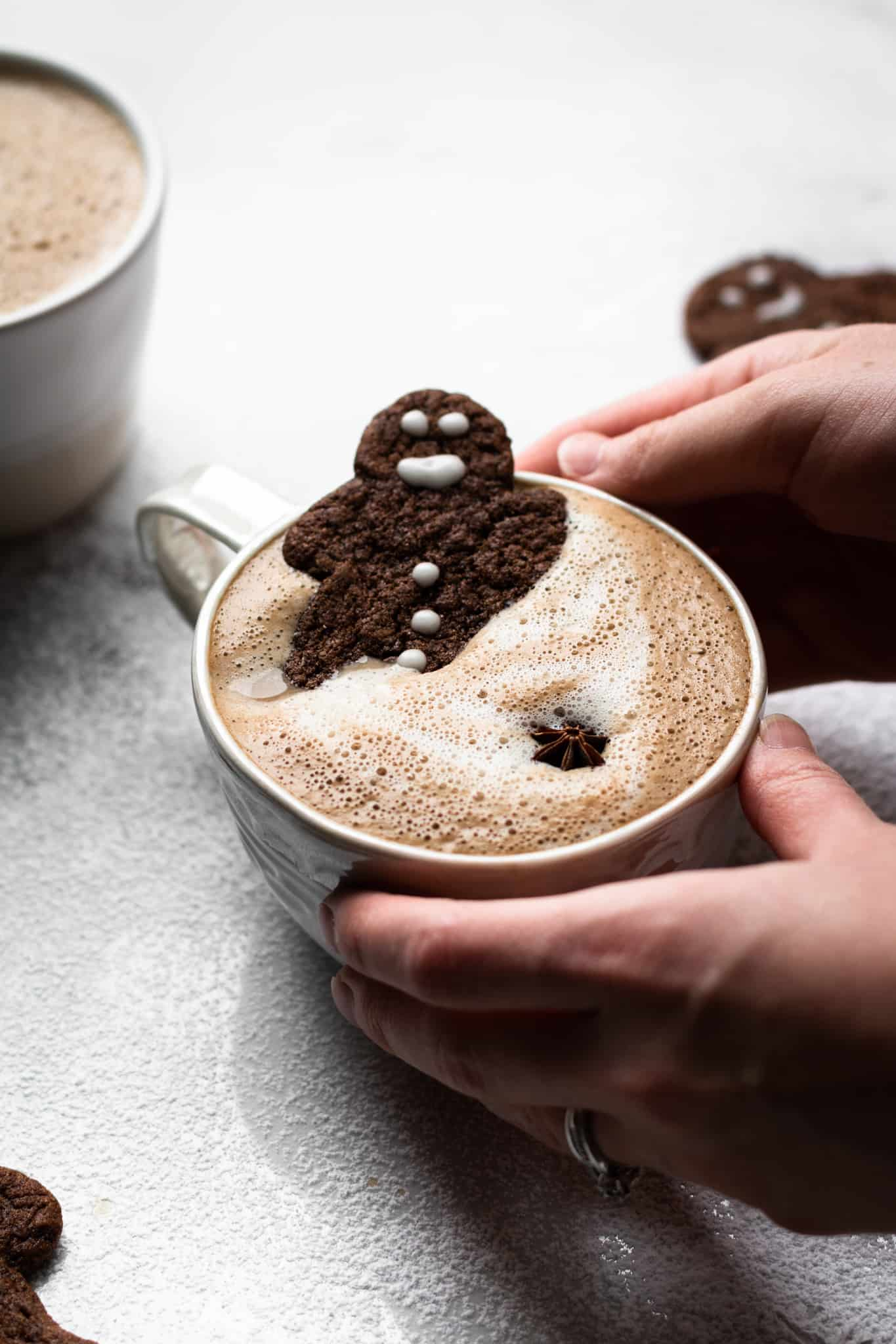 hands holding a cup of gingerbread latte