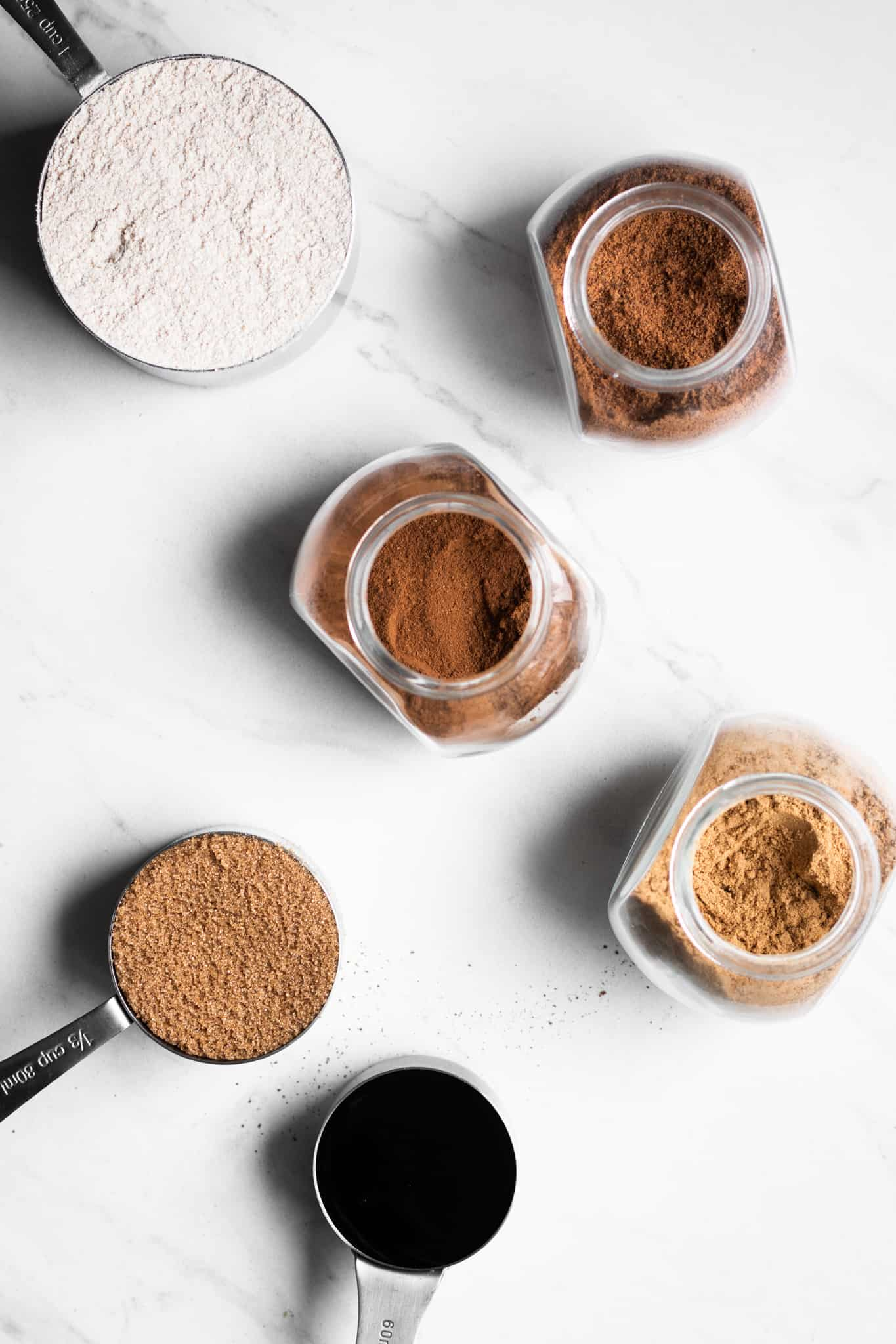 spices, flour, sugar and molasses in measuring cups and jars