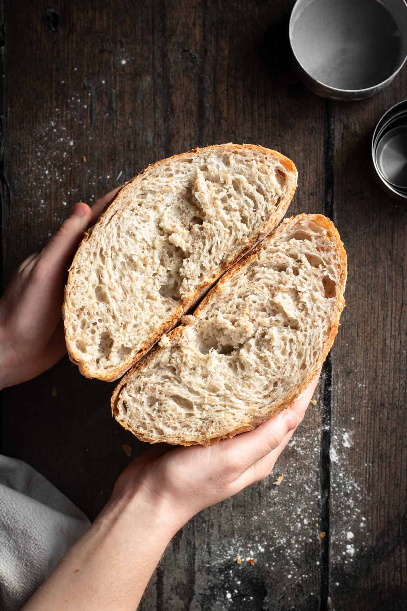 Hands holding whole wheat bread cut in half