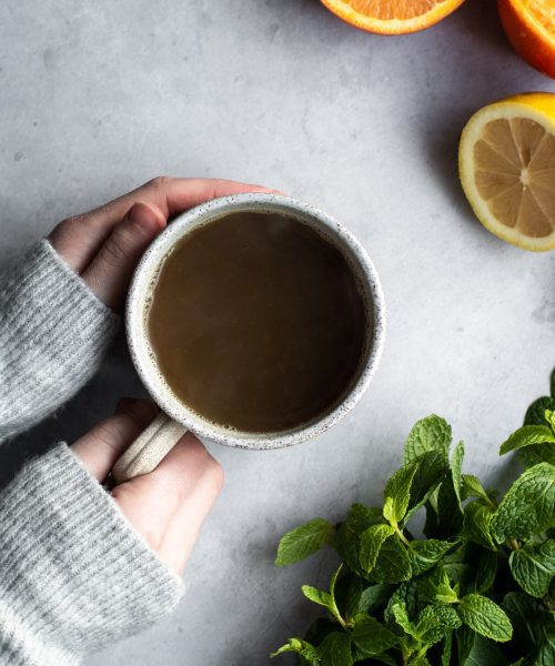 hand holding a cup of tea with citrus and mint