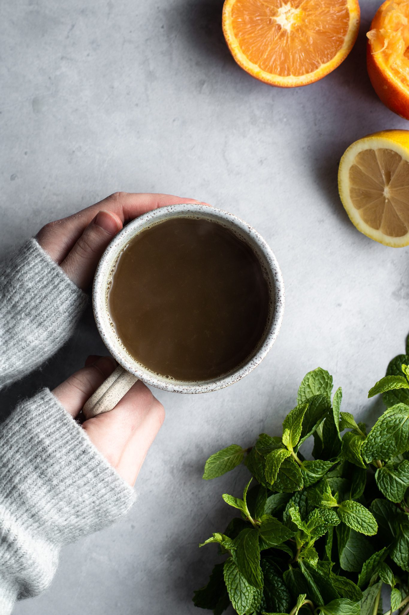hand holding a cup of citrus and mint tea