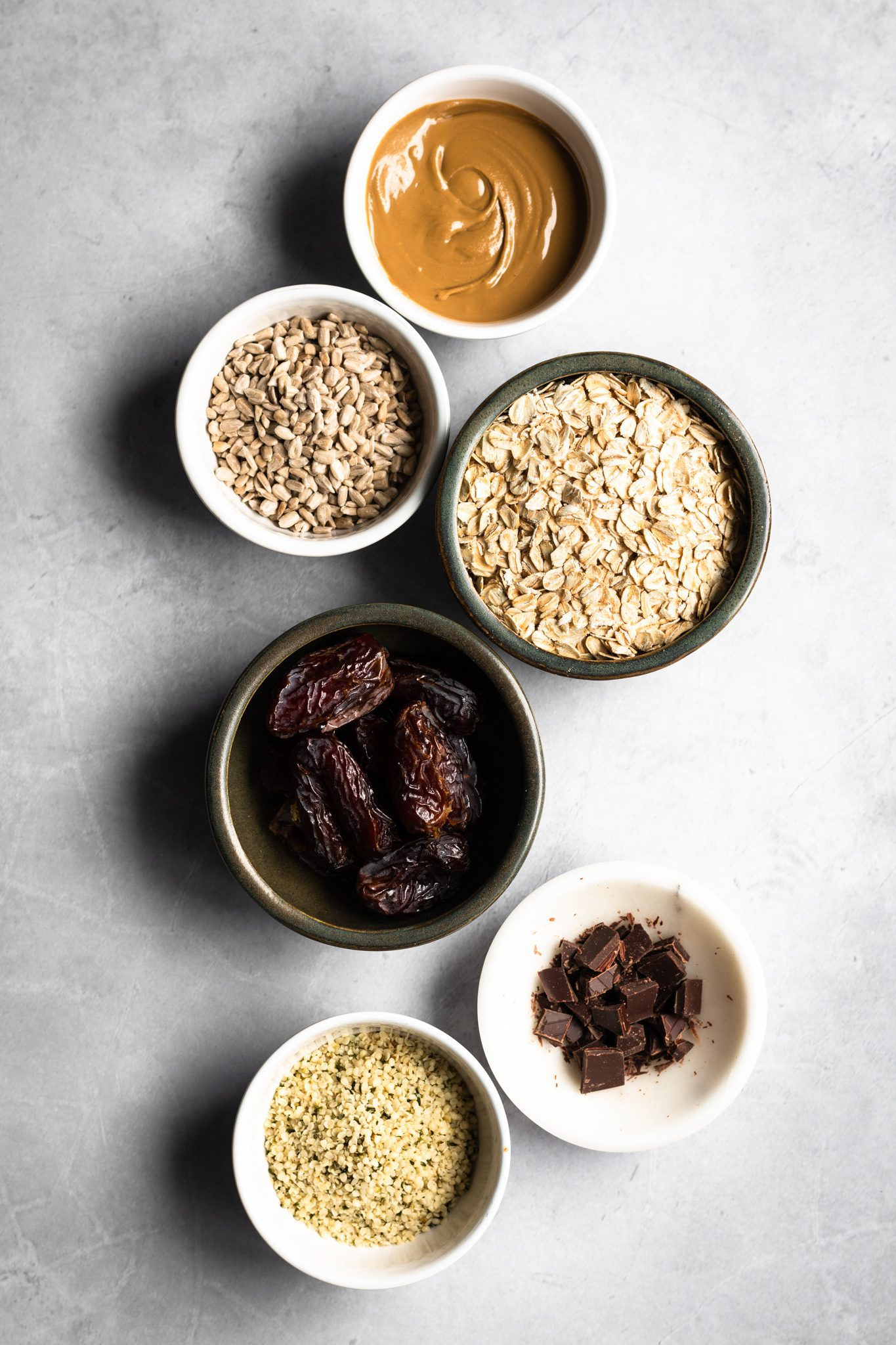 sunflower seed butter, sunflower seeds, oats, hemp hearts, dates and chocolate in bowls