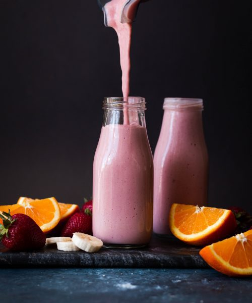 strawberry banana orange smoothie poured in a glass