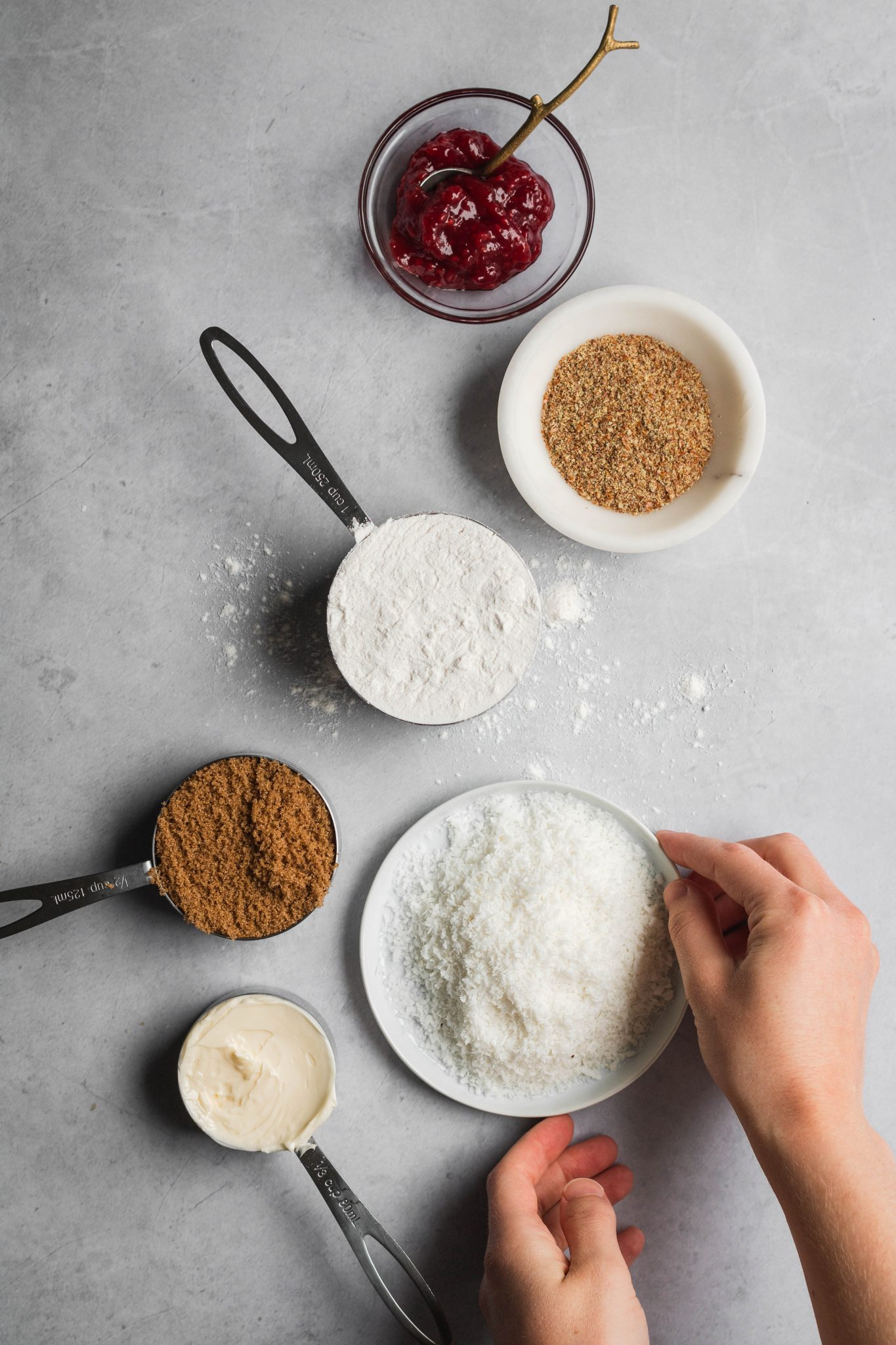 flour, coconut, sugar, butter, flax seeds and jam in bowls