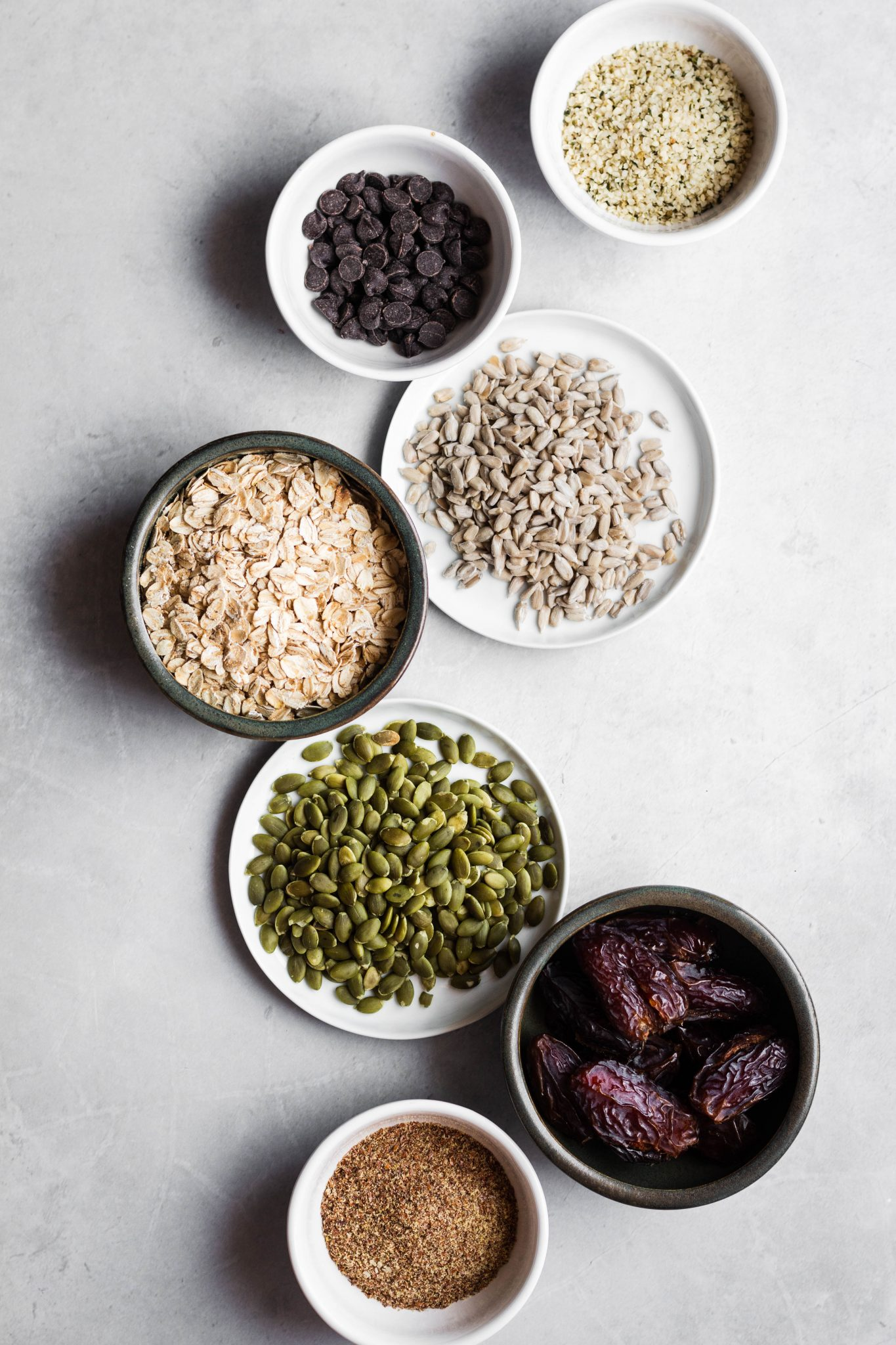seeds, oats and dates in bowls