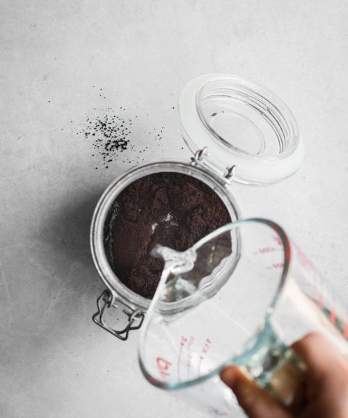 how to make cold brew coffee - water poured over coffee grounds