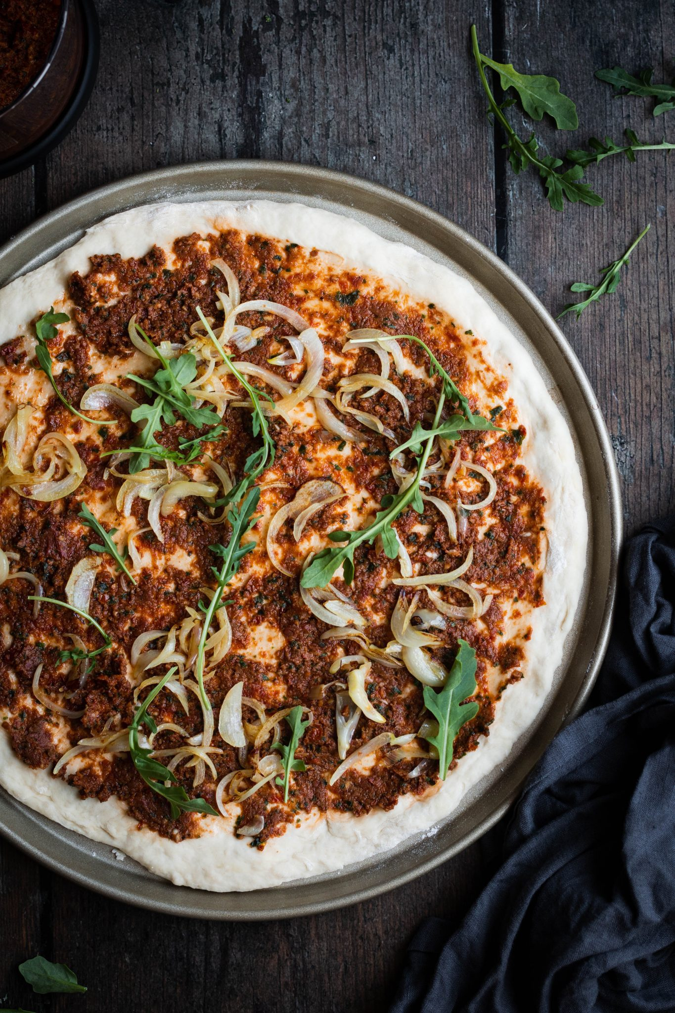 pizza dough with sun-dried tomato pesto and vegetables