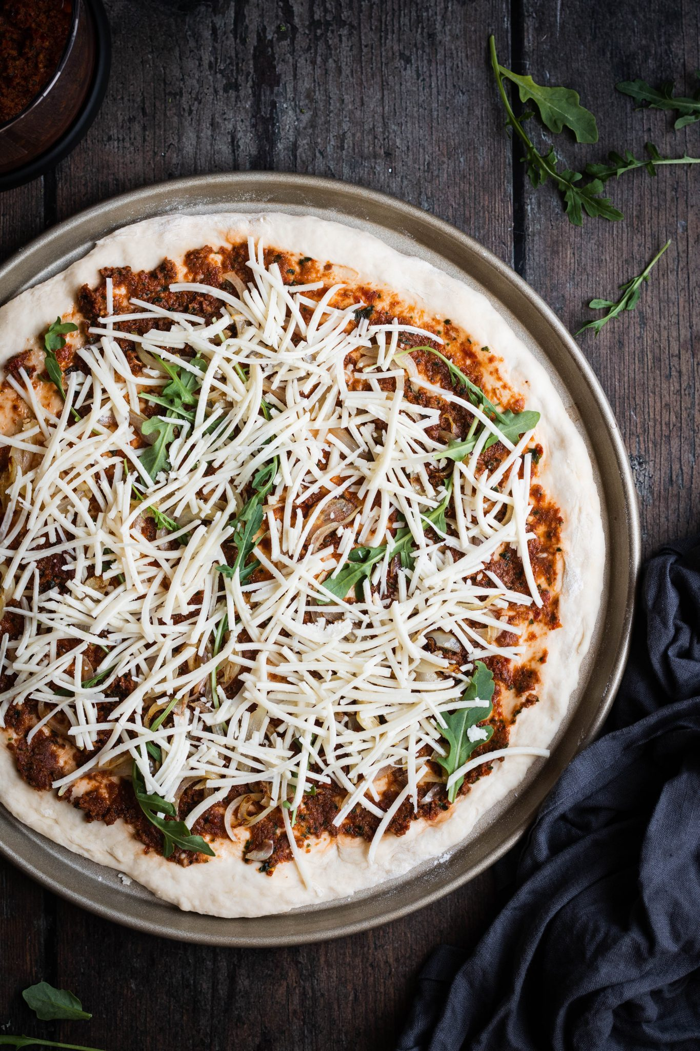 unbaked pizza with vegetables and vegan cheese